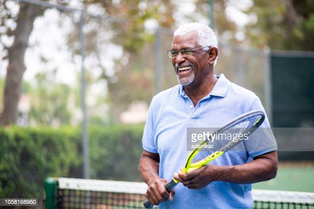 senior black man playing tennis - active seniors stock pictures, royalty-free photos & images