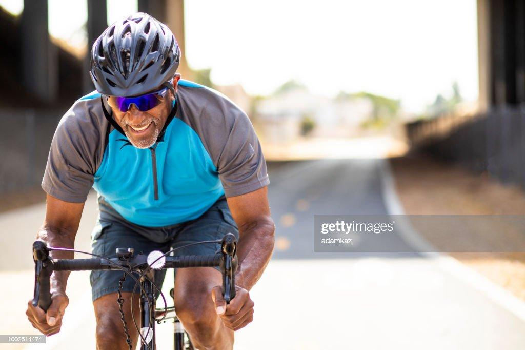 Senior Black Man Racing on a Road Bike : Stock Photo