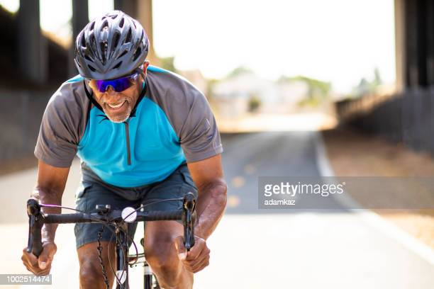 senior black man racing on a road bike - bicycle stock pictures, royalty-free photos & images