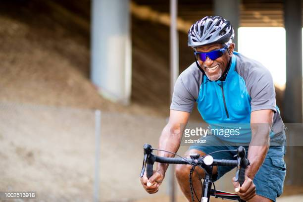 senior black man riding bike on trail - bicycle trail outdoor sports stock photos and pictures