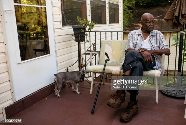 senior black man sitting on his front porch - ポーチ ストックフォトと画像