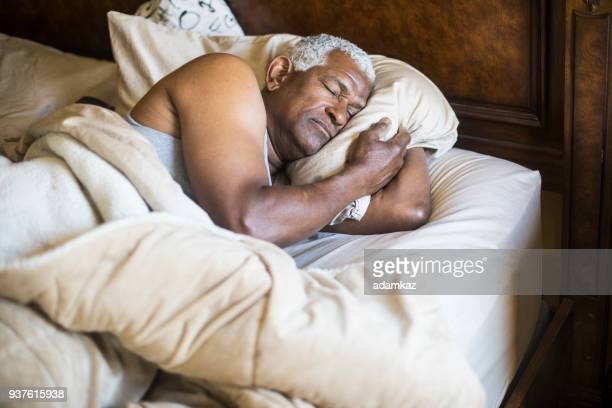 senior black man sleeping and waking up - black man sleeping in bed stock pictures, royalty-free photos & images