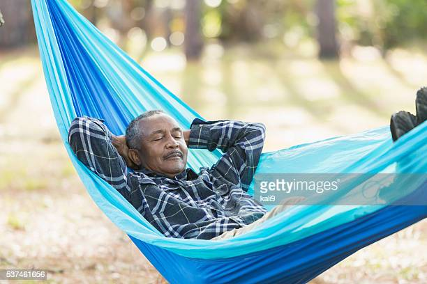 senior black man sleeping in a hammock - napping stock pictures, royalty-free photos & images