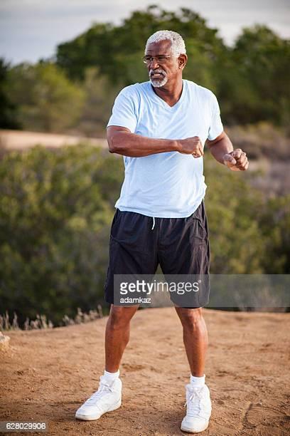 Senior Black Man Stretching and Exercising Outdoors