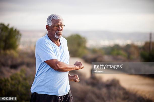 Senior Black Man Stretching and Exercising Outdoors