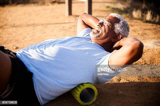 Senior Black Man Using Foam Roller