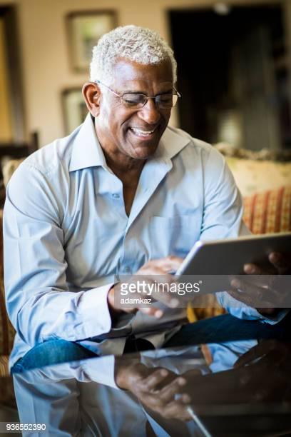Senior Black Man Using Tablet at Home