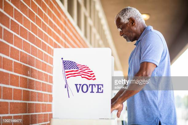 senior black man voting at booth - election stock pictures, royalty-free photos & images