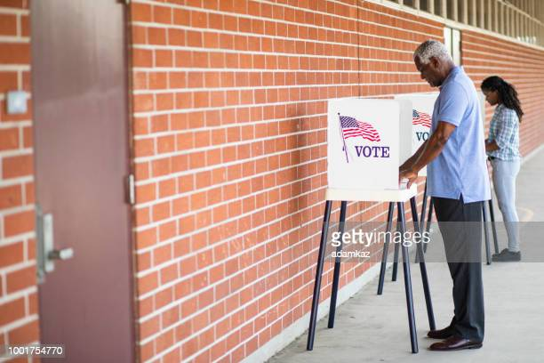 senior black man voting - american influenced stock photos and pictures