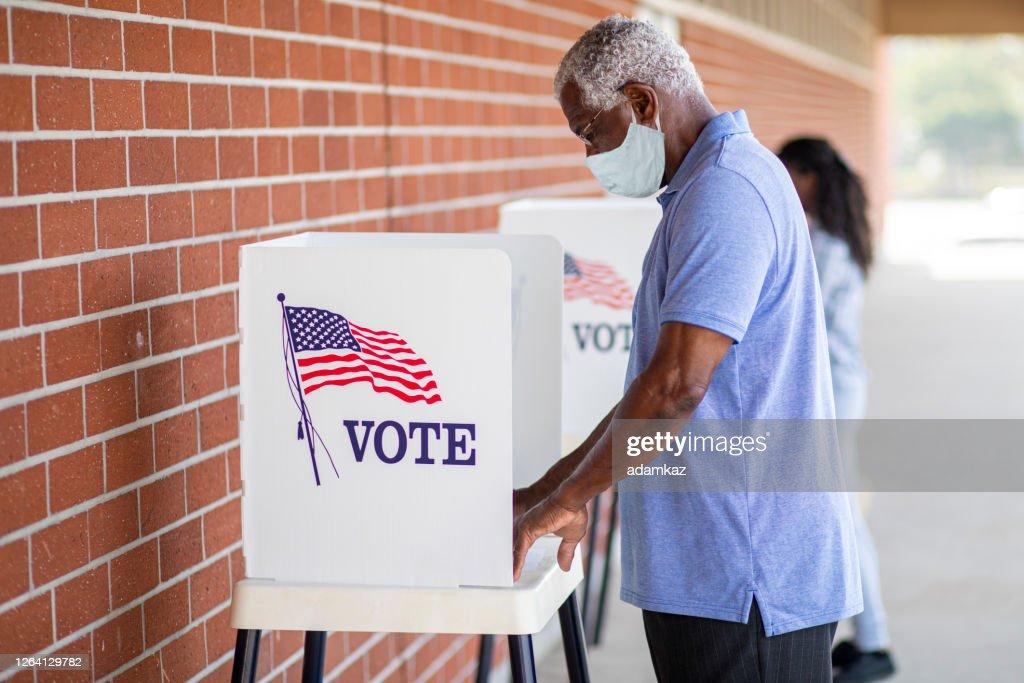 Senior Black Man Voting with a Mask : Stock Photo