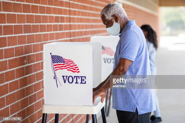 senior black man voting with a mask - election voting stock pictures, royalty-free photos & images