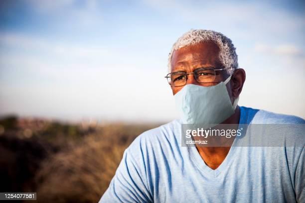 senior black man wearing a mask outdoors - adamkaz stock pictures, royalty-free photos & images