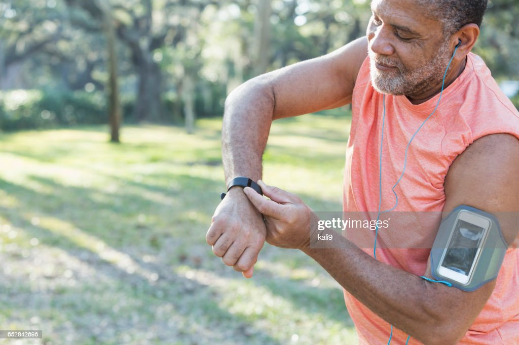 Senior black man with headphones and fitness tracker : Stock Photo