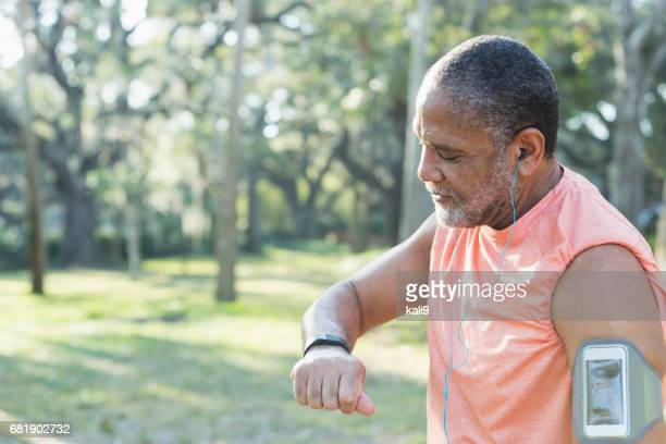 Senior black man with headphones and fitness tracker