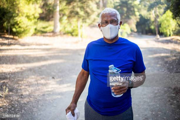 senior black man with mask - adamkaz stock pictures, royalty-free photos & images