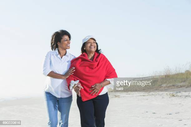 senior black woman and adult daughter walking on beach