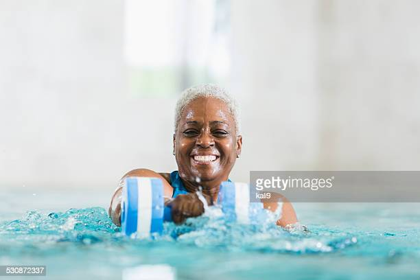 Senior black woman exercising, doing water aerobics
