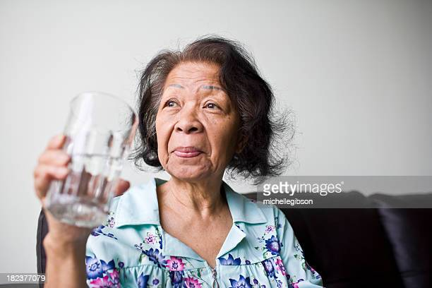senior black woman holding a glass of water - asian drink stock photos and pictures