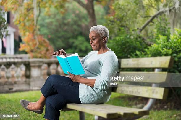 Senior mujer leyendo un libro negro