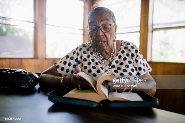 "senior black woman reading bible by going to church""n - black purse stock pictures, royalty-free photos & images"