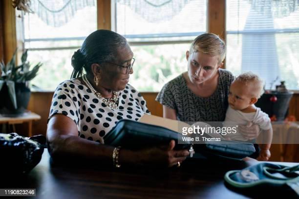 senior black woman reading bible with famliy members - be aktivitet bildbanksfoton och bilder