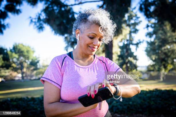 senior black woman running with a fitness tracker - adamkaz stock pictures, royalty-free photos & images