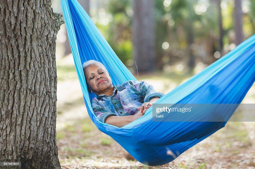 Senior black woman sleeping in a hammock : Stock Photo