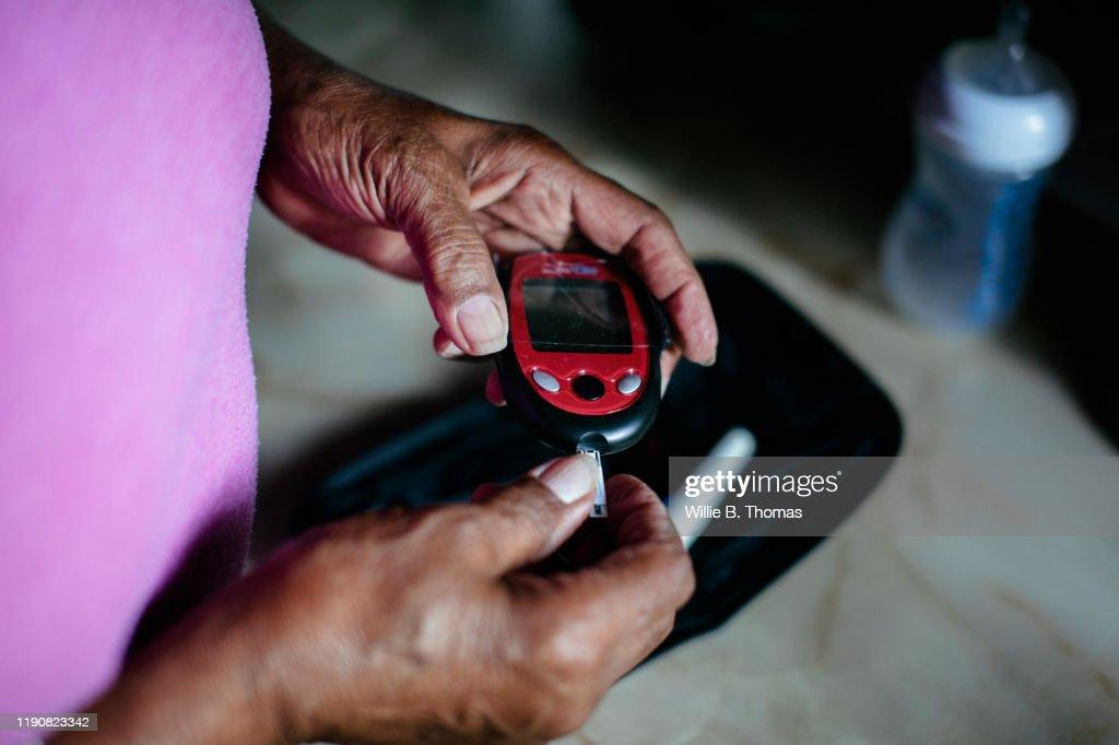 "Senior black woman using a diabetes home test kit""n : Stock Photo"