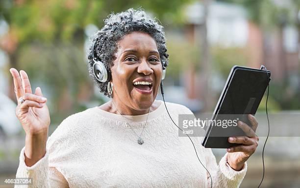Senior femme noire à l'aide de tablette numérique, Chanter