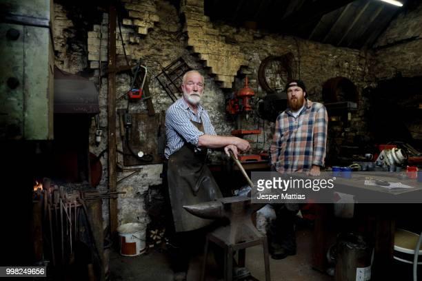 senior blacksmith and son in blacksmiths shop, portrait - don smith bildbanksfoton och bilder
