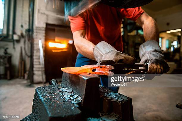 Senior blacksmith working in hammer mill