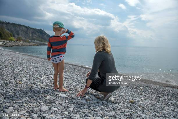 senior blond woman and her grandchild playing on a pebble beach in spring, italy - junge in unterhose stock-fotos und bilder