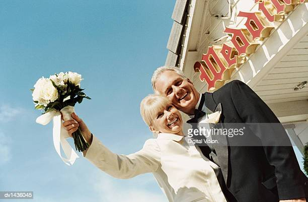 Senior Bride and Groom Standing Outside a Church Holding a Bouquet of White Roses