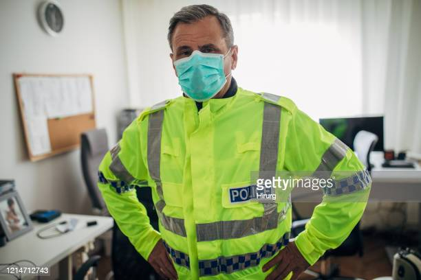senior british police officer with protective mask - police stock pictures, royalty-free photos & images