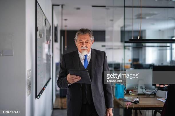 senior zakenman met behulp van digitale tablet in de kantoor zaal - alleen seniore mannen stockfoto's en -beelden
