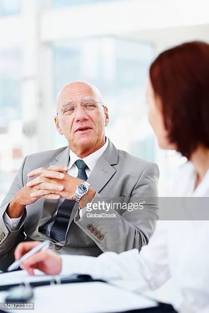 Senior business Mann mit seinem Kollegen diskutieren im Büro