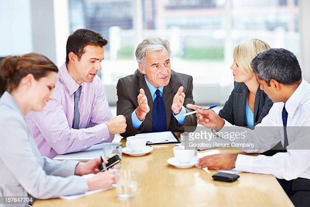 Senior business man in discussion with his team