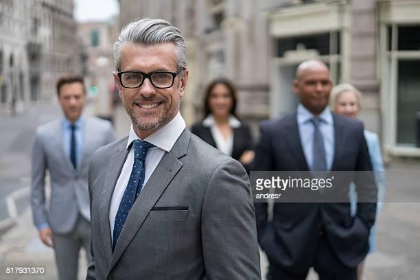 senior business man leading a group - anführen stock-fotos und bilder