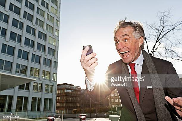 Senior business man looking at his smartphone and freaks out