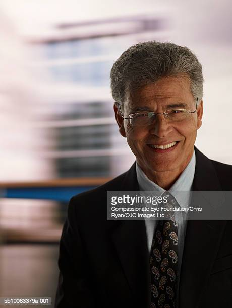Senior business man smiling, indoors, portrait