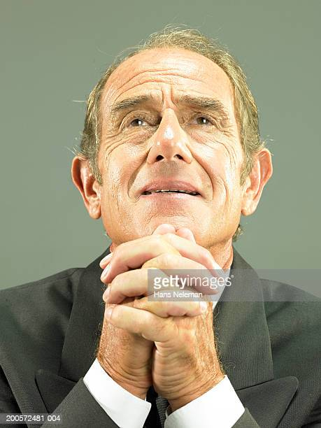 Senior business man with hands clasped, portrait