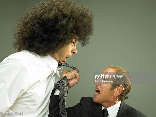 Senior business man yelling at young business man, studio shot