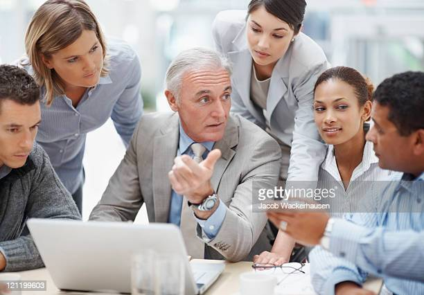 Senior business manager discussing work with his colleagues