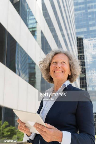 Senior business woman day dreaming looking away while holding a tablet