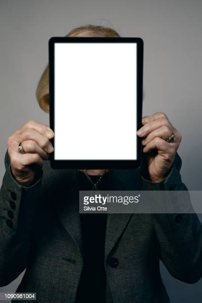 Senior business woman holding tablet in front of her face