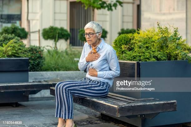 シニアビジネスウーマンは心臓の問題で気分が悪い - 喉が詰まる ストックフォトと画像