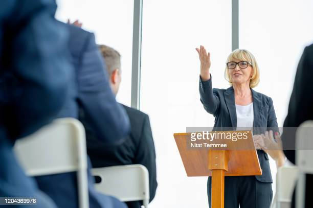 senior business woman or speaker giving a talk on corporate business conference or business seminar. - press conference stock pictures, royalty-free photos & images