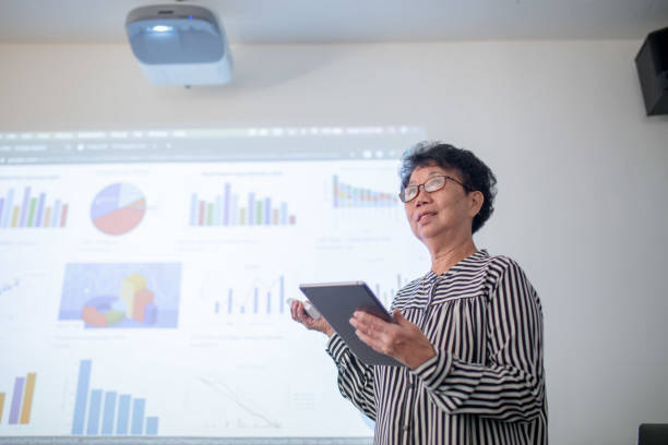 senior business woman presenting, addressing audience and standing in front of projector. - old asian woman teacher stock pictures, royalty-free photos & images
