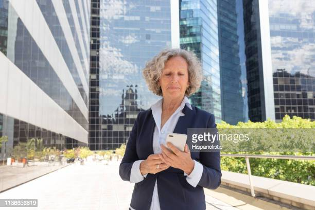 Senior business woman reading an email on smartphone looking serious