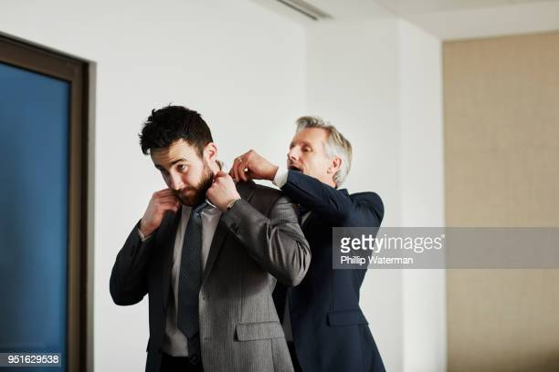senior businessman adjusting colleagues jacket in office - adjusting stock pictures, royalty-free photos & images